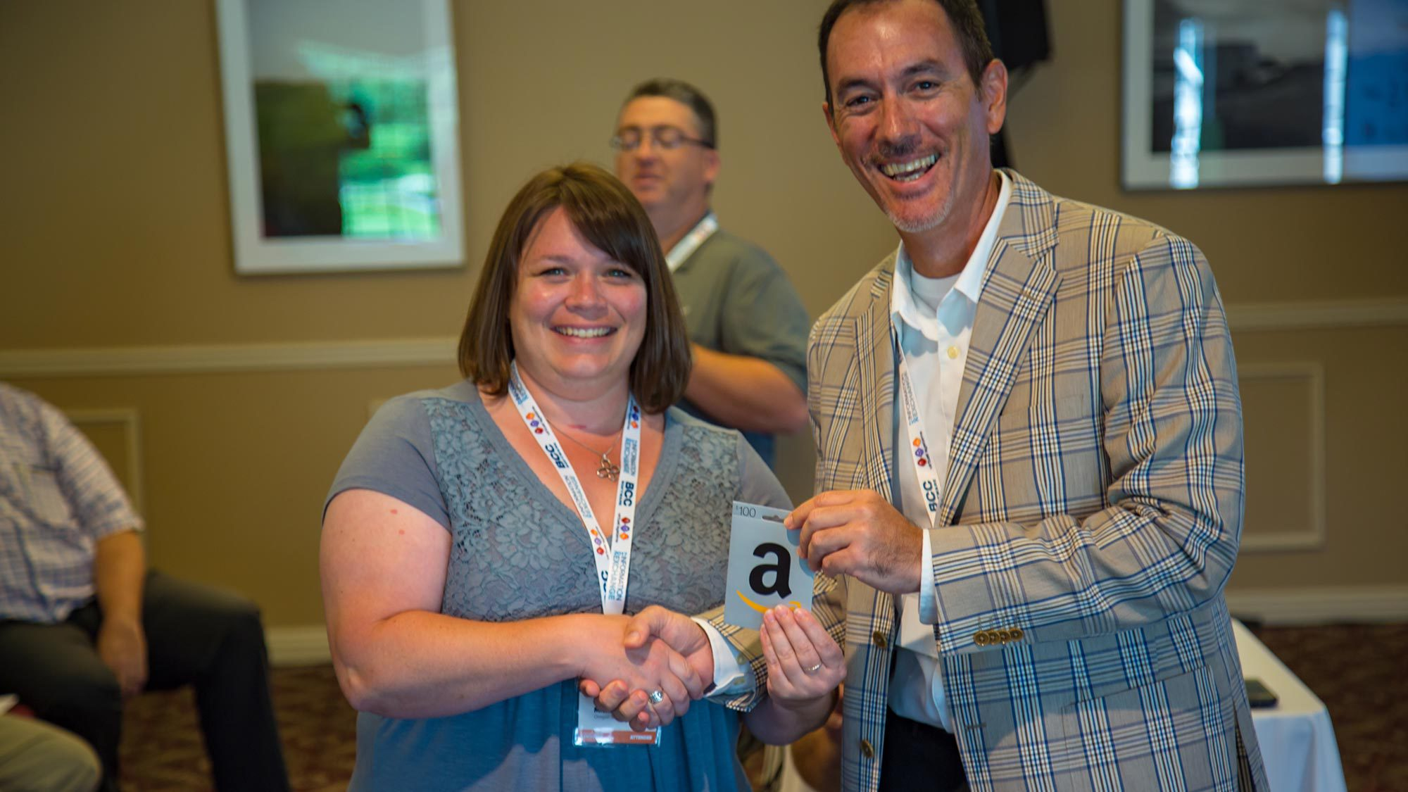 "BCC Software customer, Michelle ""Slam"" Dunks receiving her prize, an Amazon gift card from BCC Software partner, Racami."